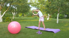 The little girl doing the physical exercises in the garden Stock Footage