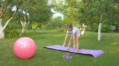A cute girl doing the exercises in the garden Stock Footage