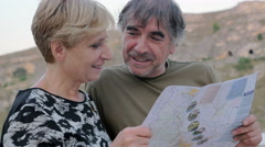 Happy middel- age couple talking quietly looking at the map Stock Footage