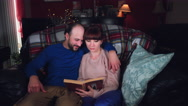 4k Authentic Shot of a Couple Reading Book on Couch Stock Footage