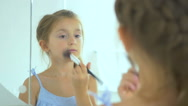 The cute girl powder the face in the mirror Stock Footage