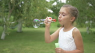 A cute girl blows a bubbles in the garden. Stock Footage