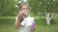 A sweet girl blows a bubbles in the garden Stock Footage