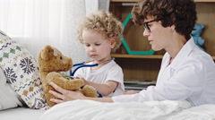 Toddler Playing Doctor with Plush Bear Stock Footage