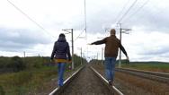 Couple walking on railroad tracks Stock Footage