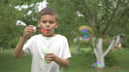 The boy blows a bubbles in the garden Stock Footage