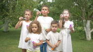 Little kids blows the bubbles in the garden Stock Footage
