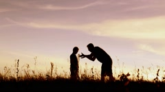 Angry parent and his child over sunset sky background Stock Footage