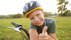 Child in cycle helmet posing for camera near his bike. Stock Footage