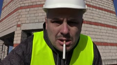 Worker with cigarette in mouth look to camera and touching eye Stock Footage