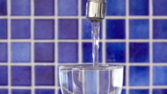 Water flowing from tap in a glass that is overflowing Stock Footage