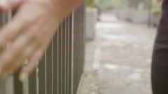 Silhouette of woman walking by touching the bars of a gate Stock Footage