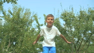 The happy boy jumping on the trampoline in the garden Stock Footage