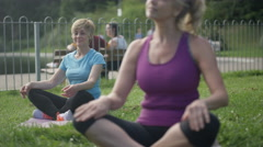 4K Happy mature female friends doing yoga & meditating in the park Stock Footage