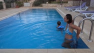 Mother and son enter swimming pool and swim Stock Footage
