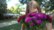 Happy Girl holds a Bunch of Flowers in City Park Stock Footage
