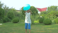 Boy blows the ball by the foot on the grass Stock Footage