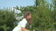 A beautiful girl is jumping on the trampoline in the garden Stock Footage