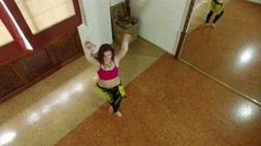 A red-haired attractive girl performing a belly dance. Wide angle. Top view. 4K Stock Footage