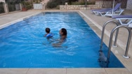 Mother and son swimming in swimming pool Stock Footage