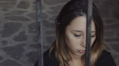 sad and thoughtful woman behind bars Stock Footage
