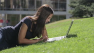 Young beautiful woman in the park with a laptop. Stock Footage
