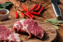 Two steak with chili, cayenne powder and other condiment Stock Photos