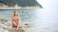 Girl in bikini drink juice through a straw. woman at the sea. Stock Footage