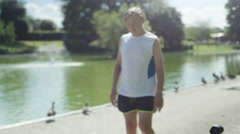 4K Senior man takes a break from exercising in the park & looks out over lake Stock Footage