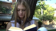Cute Blonde Girl reading a Book during a Picnic in the Park sunny Day Stock Footage