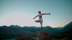 4K beautiful girl in white clothes doing yoga on the beautiful backdrop of the Stock Footage