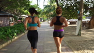 Close-up view young caucasian women are running for a jog on the sidewalk along Stock Footage