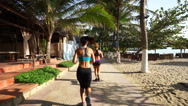 Young caucasian women are running races on the sidewalk along coastline near Stock Footage