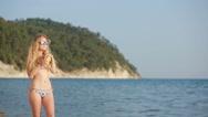 Girl in bikini drink juice through a straw. woman at the sea. calling to him Stock Footage