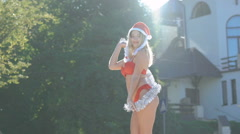 Glamour girl in santa hat dancing with Christmas decoration in sunny day. Slowly Stock Footage