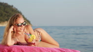 Girl in bikini drink juice through a straw. woman at the sea. Stock Footage