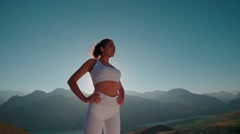 Beautiful girl in white clothes, reaching the top of the mountain stands and Stock Footage