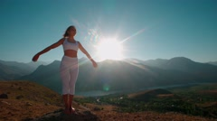 Beautiful girl in white clothes, reaching the top of the mountain raises his Stock Footage