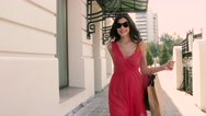 Happy brunette in a red dress and sunglasses Stock Footage