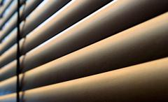 Closeup of wooden slats of a blind with natural sunshine shining through the  Stock Photos