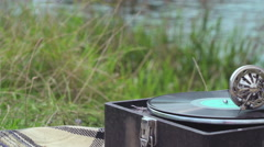 Umbrella and the gramophone on a retro picnic by the river 5 Stock Footage