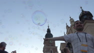 Many bubbles floating on public square - Happy people - low angle shot Stock Footage