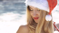 Girl in red swimsuit and santa hat flirting and posing on the beach. Slowly Stock Footage