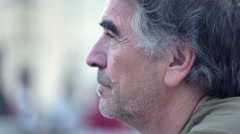 Profile of middle-aged man who looks around thoughtfully Stock Footage
