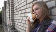 Hungry Blonde Girl eating a Sandwich Hamburger at a brick Wall Stock Footage