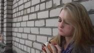 Hungry Blonde Girl eating a Sandwich Hamburger at a brick Wall Stock Footage