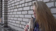 Upset drunk Girl Blonde drinking Beer from a Bottle eating sandwich by the Wall Stock Footage