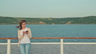 Woman using mobile phone on deck of cruise ship Stock Footage