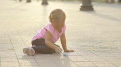 A little girl drawing on pavement with chalk Stock Footage