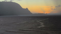 Sun setting behind mountain and misty rain clouds over ocean at Hanalei in Kauai Stock Footage